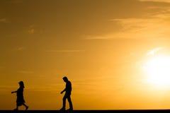 La gente della siluetta che cammina al tramonto Immagine Stock