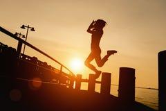 La gente della siluetta che salta nel tramonto Fotografia Stock