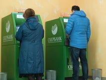 La gente delle generazioni differenti usa i servizi di ATMs di Sberbank fotografia stock libera da diritti