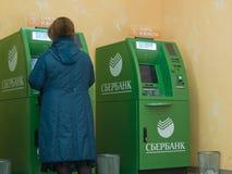 La gente delle generazioni differenti usa i servizi di ATMs di Sberbank fotografie stock