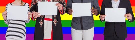 La gente delle nazionalità differenti sta tenendo gli strati vuoti contro lo sfondo della bandiera di LGBT Il concetto di fotografia stock