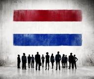 La gente delle siluette che esamina la bandiera dei Paesi Bassi Immagini Stock Libere da Diritti