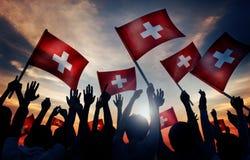 La gente delle siluette che tiene concetto della Svizzera della bandiera Fotografia Stock Libera da Diritti
