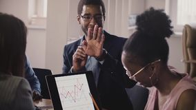 La gente di affari afroamericana parla, mostra i gesti e comunica alla riunione dell'ufficio, esaminante i diagrammi del computer stock footage