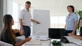 La gente di affari ascolta del collega maschio che dà la presentazione in ufficio bianco e spazioso archivi video
