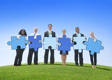 La gente di affari che tiene il puzzle collega all'aperto immagini stock libere da diritti