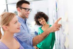 La gente di affari discute i dati a bordo Immagini Stock