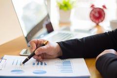 La gente di affari indica i grafici ed i grafici di cui mostri i risultati fotografia stock