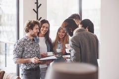 La gente di affari riuscita sta utilizzando gli aggeggi, sta parlando e sorridendo durante la pausa caffè in ufficio fotografie stock libere da diritti
