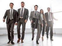 La gente di affari scende il corridoio di un ufficio moderno immagine stock libera da diritti