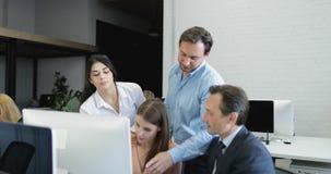 La gente di affari unisce i colleghi che lavorano al computer nella discussione su nuova strategia per la partenza, gruppo che an video d archivio