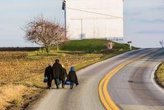 La gente di Amish che cammina sulla strada rurale nel PA della contea di Lancaster immagine stock libera da diritti