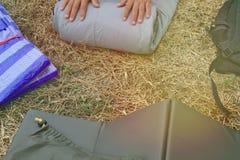 La gente di campeggio del sacco a pelo dell'attrezzatura è sacchi a pelo dei rotoli da immagazzinare fotografia stock libera da diritti