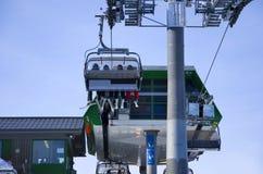 La gente di corsa con gli sci nell'elevatore di pattino Immagine Stock