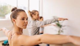La gente di forma fisica che fa yoga nella classe della palestra Fotografia Stock