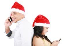 La gente di natale felice che usando mobile Fotografie Stock