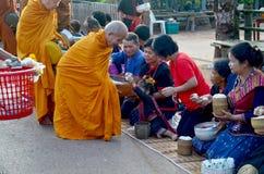 La gente di Phu tai che prepara alimento ed almsgiving con riso appiccicoso Immagine Stock
