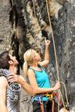 La gente di scalata di roccia che sembra indicante in su Immagini Stock