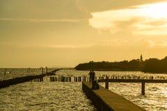 La gente di Sihouette al passaggio pedonale concreto sulla vacanza per seaview nel tramonto con luce solare Immagine Stock