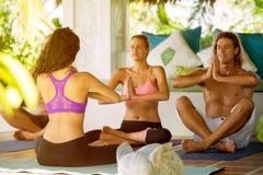 La gente di yoga nel meditare della classe A Fotografia Stock Libera da Diritti