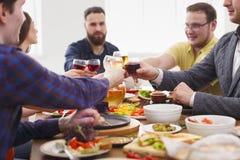 La gente dice i vetri del tintinnio di acclamazioni al partito di cena festivo della tavola Fotografia Stock Libera da Diritti