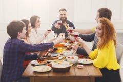 La gente dice i vetri del tintinnio di acclamazioni al partito di cena festivo della tavola Fotografie Stock Libere da Diritti