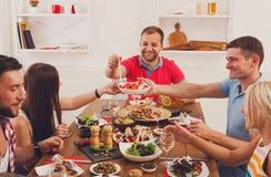 La gente dice los vidrios del tintineo de las alegrías en el partido de cena festivo de la tabla Fotos de archivo