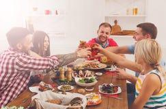 La gente dice los vidrios del tintineo de las alegrías en el partido de cena festivo de la tabla Fotografía de archivo