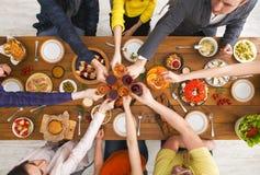 La gente dice los vidrios del tintineo de las alegrías en el partido de cena festivo de la tabla Imagen de archivo