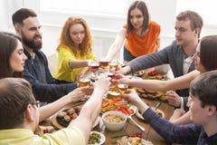 La gente dice los vidrios del tintineo de las alegrías en el partido de cena festivo de la tabla Fotos de archivo libres de regalías