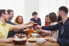 La gente dice los vidrios del tintineo de las alegrías en el partido de cena festivo de la tabla Fotografía de archivo libre de regalías