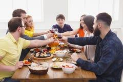 La gente dice los vidrios del tintineo de las alegrías en el partido de cena festivo de la tabla Imágenes de archivo libres de regalías