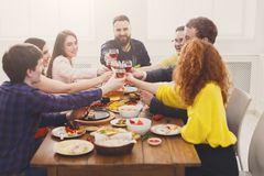 La gente dice los vidrios del tintineo de las alegrías en el partido de cena festivo de la tabla Foto de archivo