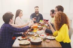 La gente dice los vidrios del tintineo de las alegrías en el partido de cena festivo de la tabla Foto de archivo libre de regalías