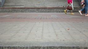 La gente differente che cammina sulle mattonelle della pavimentazione della città, piedi della folla cammina stock footage