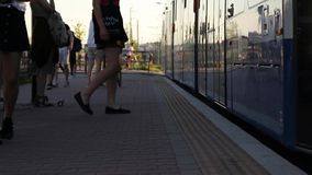 La gente differente dell'età prevede il trasporto alla fermata dell'autobus Decolli la fine dei piedi della gente entrano in tram stock footage