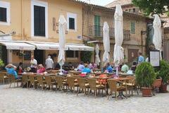 La gente disfruta de sus bebidas en una terraza rústica en Valldemossa, Mallorca Fotos de archivo libres de regalías