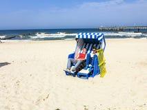 La gente disfruta del sunbath en la silla de playa de mimbre cubierta imagenes de archivo