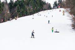 La gente divertendosi corsa con gli sci sulla montagna di Snowy Fotografia Stock