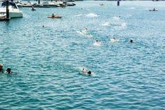 La gente divertendosi nuotando nella spiaggia blu intorno al porticciolo durante l'estate immagini stock libere da diritti