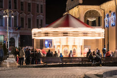 La gente divertendosi sul carosello della zona fieristica di Natale Immagine Stock