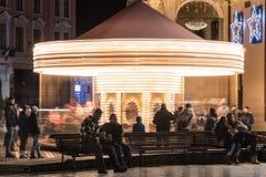 La gente divertendosi sul carosello della zona fieristica di Natale Fotografia Stock Libera da Diritti