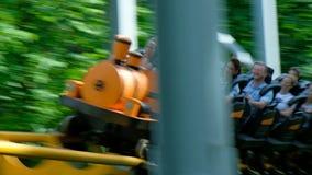 La gente divertida monta la montaña rusa colorida moderna en parque almacen de video