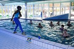 La gente durante la forma fisica di addestramento di Zumba dell'acqua ad una palestra Immagini Stock