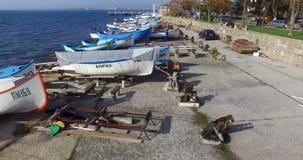 La gente e barche nel porto dell'autunno Pomorie di Mar Nero in Bulgaria stock footage