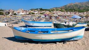 La gente e barche sulla spiaggia urbana in Giardini Naxos Fotografia Stock