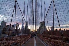 La gente e bicicletta sul ponte di Brooklyn al tramonto immagine stock