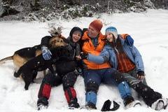 La gente e cani in neve Immagini Stock