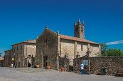 La gente e chiesa al villaggio di Monteriggioni Fotografia Stock