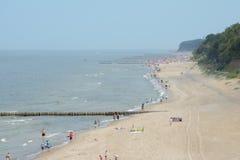 La gente e frangiflutti di legno sulla spiaggia in Trzesacz e in Rewal, Polonia Fotografia Stock